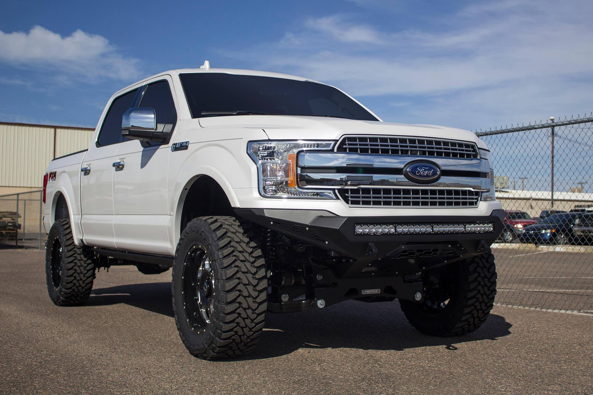 White lifted ford f 150 with fabtech off road front bumper photo by