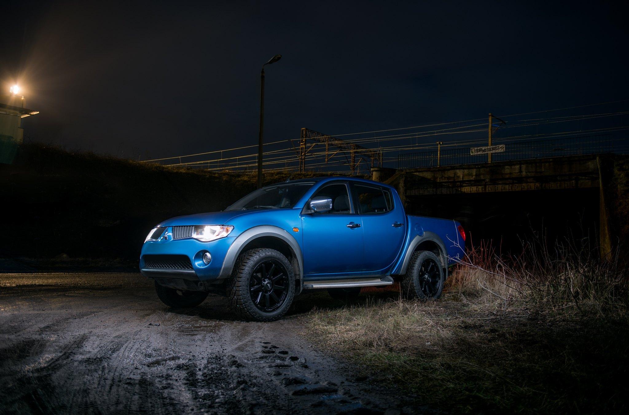 custom blue mitsubishi l200 resting on goodyear tires — carid